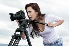 Young professional woman photographer. Female photographer with camera and tripod Royalty Free Stock Photo