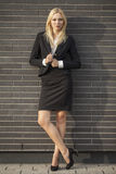 Young professional woman projecting confidence. Young professional in business attire projecting confidence against brick wall royalty free stock image