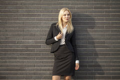 Young professional woman projecting confidence. Young professional in business attire projecting confidence against brick wall royalty free stock photos