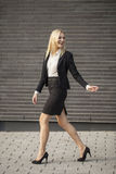 Young professional woman projecting confidence. Young professional in business attire projecting confidence against brick wall royalty free stock photo
