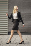 Young professional woman projecting confidence. Young professional in business attire projecting confidence against brick wall stock photo