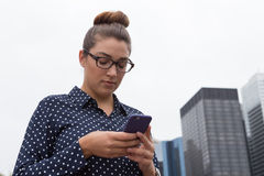 Young professional woman texting in the city Royalty Free Stock Photo