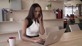 Young professional woman at work. Mixed race businesswoman sitting at the working place in modern office. Smiling contemporary manager has phone conversation stock video footage