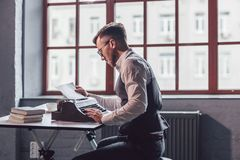 Young professional at work. Young professional with a retro typewriter at work royalty free stock images
