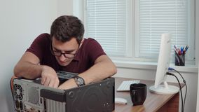 Young professional worker repair a broken computer in the office using a screwdriver and upgrading computer hardware. Support team. Computer maintenance. Shot stock footage