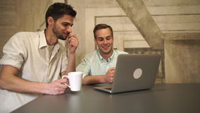 Young professional working team. Two men discussing future project. Pair of happy workers with computer communicate. Handsome caucasian man and mixed race male stock video footage