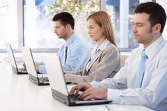 Young professionals busy by working. Using laptop in meeting room royalty free stock image