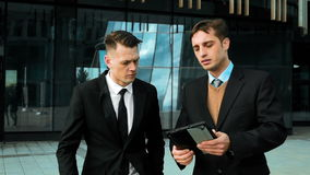 Young professionals discussing business outdoor. Slow motion: Two white young managers with tablet pc finding interesting site in Internet network wi-fi. Glass stock video footage