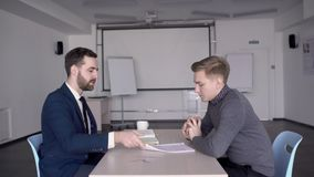 Young professionals are discussing new project at table in large company. Two men talking in working process, sitting at desk in modern office. Business people stock footage