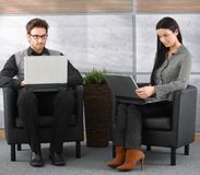 Young professionals in office lobby with laptop. Young professionals sitting in office lobby, working on laptop royalty free stock photos
