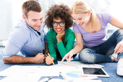 Young professionals sitting on floor discussing papers Royalty Free Stock Image