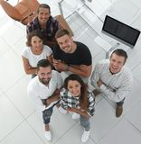 Young professionals standing near the desktop. View the top. a group of young professionals standing near the desktop and looking up stock photos
