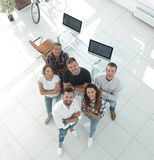 Young professionals standing near the desktop. View the top. a group of young professionals standing near the desktop and looking up Stock Photography