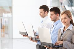 Young professionals using laptop in office lobby Stock Photos