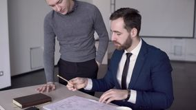 Young professionals work on blueprint at table in modern office. Two business persons are in workflow with documents at desk in leading company. Men are stock video