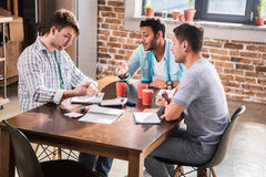 Young professionals working on business project together. Group of young professionals working on business project together royalty free stock image