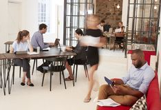 Young professionals working in a busy open plan office Stock Photos