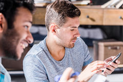 Young professionals working in small business office. Men using smartphone royalty free stock images