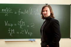 Young professor. Against blackboard in classroom stock photography