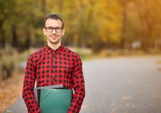 Young professor in glasses holding folders in autumn park. Knowledge concept royalty free stock photography