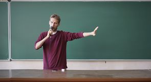 Young professor teacher speaking with the microphone in the lecture hall standing near blackboard. Young professor teacher speaking with the microphone in the stock images