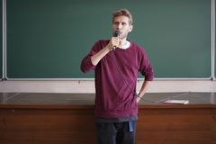Young professor teacher speaking with the microphone in the lecture hall standing near blackboard. Young professor teacher speaking with the microphone in the stock photography