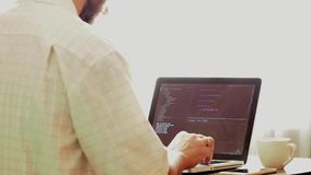 Young programmer coding on a laptop in office