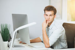 A young programmer is looking at the camera. The graphic designer is thinking about the future projects. The young guy. Is sitting at the computer in the office Stock Image