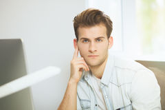 A young programmer is looking at the camera. The graphic designer is thinking about the future projects. The young guy. Is sitting at the computer in the office Royalty Free Stock Photos