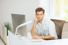 A young programmer is looking at the camera. The graphic designer is thinking about the future projects. The young guy. Is sitting at the computer in the office Royalty Free Stock Photography