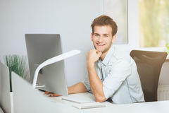 A young programmer is looking at the camera. The graphic designer is thinking about the future projects. The young guy. Is sitting at the computer in the office Stock Images