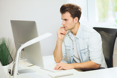 A young programmer is looking at the camera. The graphic designer is thinking about the future projects. The young guy. Is sitting at the computer in the office Royalty Free Stock Images
