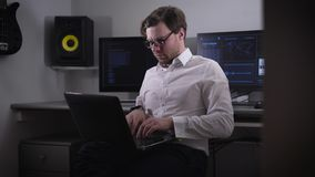 Young programmer in a white shirt and stylish glasses working on a laptop that is on his knees on the background several stock footage