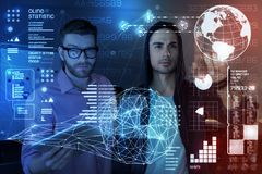 Young programmers using security application. Open cyber space. Professional programmers touching transparent screen while providing security Stock Images