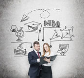 Young prosperous couple are thinking about MBA degree and checking some information in the black folder. Educational chart is draw. N behind them. A concept of Stock Photo
