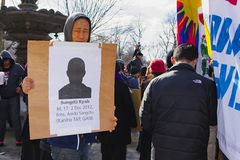 Young protestor in hoodie. Boston, Massachusetts USA - March 2013 - Young man holding up picture and caption of self immolation victim during the Boston Free Royalty Free Stock Photo
