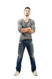 Young proud man with crossed arms looking at camera. Young proud satisfied man with crossed arms looking at camera. Full body length isolated over white royalty free stock photo
