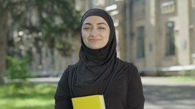 Young proud Muslim woman in traditional black hijab posing on sunny day at university yard. Portrait of confident female