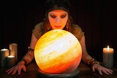 Young Psychic is telling the future, crystal ball and candles in. Young beautiful Psychic is telling the future, crystal ball and candles in front of black Royalty Free Stock Photo