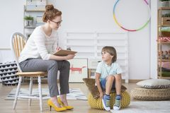 Young psychotherapist with child. Young psychotherapist sitting on a chair with a child who has a problems with education Stock Photo