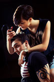 Young punk girl cuts her boyfriend. Using clippers Stock Photography