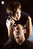Young punk girl cuts her boyfriend. Using clippers Royalty Free Stock Photo