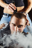 Young punk girl cuts her boyfriend. Using clippers Royalty Free Stock Image