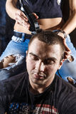 Young punk girl cuts her boyfriend. Using clippers Stock Photos