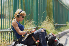 Young punk girl skater in headphones. Punk skater chick in torn jeans mounting her board while sitting in trendy wireless headphones outdoors Stock Photo