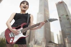 Young Punk Rock Girl Singing and Playing Guitar royalty free stock photos