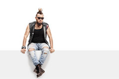 Young punk rocker with a Mohawk hairstyle. And a leather vest sitting on a panel isolated on white background Stock Photos
