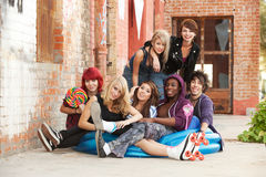 Young punk teens posing for a group shot. Young and crazy punk teens pose for a gorup shot behind an abandoned building downtown Royalty Free Stock Photography