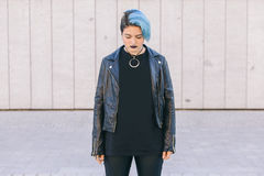 young punk woman with blue dyed hair and a leather jacket looking down stock photo