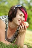 Young punk woman eating an apple Stock Photography